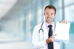 Doctor sonriente feliz con el tablero que se coloca en vestíbulo del hospital Imágenes de archivo libres de regalías