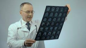Doctor sonriente feliz que comprueba la exploración de cerebro de MRI, satisfecha con resultados de tratamiento almacen de video