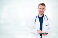 Doctor sonriente joven hermoso con el tablero Fotos de archivo libres de regalías