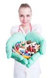 Doctor sonriente joven que sostiene muchas píldoras en sus palmas Fotos de archivo libres de regalías