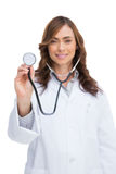 Doctor sonriente que celebra el estetoscopio y la mirada de la cámara imagenes de archivo