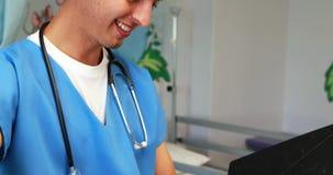 Doctor sonriente que comprueba informe médico en hospital almacen de metraje de vídeo