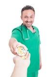 Doctor sonriente que da píldoras al paciente Imagenes de archivo