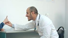 Doctor sonriente que da a pequeño paciente una piruleta después del examen Fotos de archivo libres de regalías