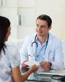 Doctor sonriente que da una prescripción Imagenes de archivo