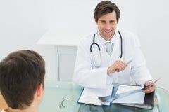 Doctor sonriente que explica informes de la radiografía al paciente imagen de archivo libre de regalías