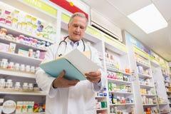 Doctor sonriente que lee una prescripción Imagenes de archivo