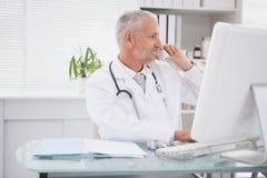 Doctor sonriente que llama por teléfono y que usa al ordenador fotos de archivo