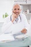 Doctor sonriente que llama por teléfono y que usa al ordenador fotografía de archivo libre de regalías