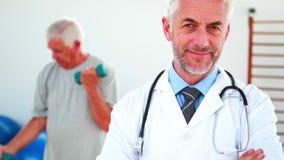 Doctor sonriente que mira la cámara con el paciente que ejercita en fondo almacen de video