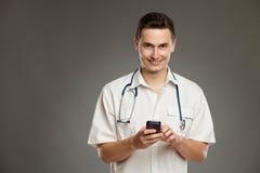 Doctor sonriente que presenta con el teléfono móvil Fotos de archivo libres de regalías
