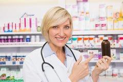 Doctor sonriente que señala una botella de la droga Imágenes de archivo libres de regalías