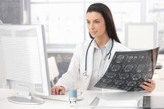 Doctor sonriente que trabaja en el escritorio Imagen de archivo