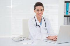 Doctor sonriente que usa el ordenador portátil Fotografía de archivo libre de regalías