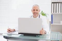 Doctor sonriente que usa el ordenador portátil y la escritura Fotografía de archivo libre de regalías
