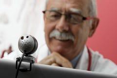 Doctor sonriente que usa el webcam Imágenes de archivo libres de regalías