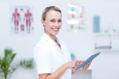 Doctor sonriente que usa la tableta fotos de archivo