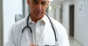 Doctor sonriente que usa la tableta digital en pasillo almacen de metraje de vídeo