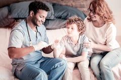 Doctor sonriente que venda la mano del paciente joven Fotografía de archivo libre de regalías