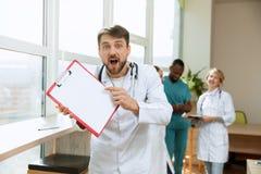 Doctor sorprendido hermoso sobre fondo del hospital fotos de archivo