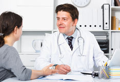 Doctor speaking with client in the medical center. Young  doctor speaking with client in the medical center Stock Photography
