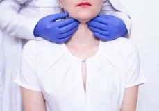 Doctor specialist diagnoses palpation on the throat of the caucasian girl for the presence of enlarged lymph nodes and. Tumors, adenoids, discomfort royalty free stock photo