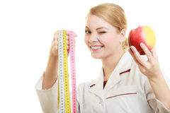 Doctor specialist holding fruit apple and measure tape Stock Photos