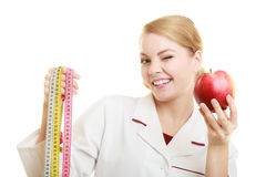 Doctor specialist holding fruit apple and measure tape Royalty Free Stock Photos