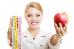 Doctor specialist holding fruit apple and measure tape Royalty Free Stock Images