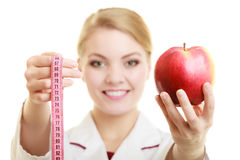 Doctor specialist holding fruit apple and measure tape Royalty Free Stock Photo