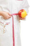 Doctor specialist holding fruit apple measuring waist Royalty Free Stock Photography