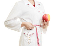 Doctor specialist holding fruit apple measuring waist Royalty Free Stock Image