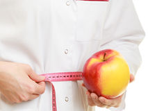 Doctor specialist holding fruit apple measuring waist Stock Photography
