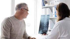 Doctor with spine x-ray and senior man at hospital 72. Medicine, healthcare, surgery, radiology and people concept - doctor showing x-ray of spine to senior man stock video footage