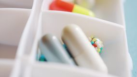 A doctor spreads out pills and medication for the week using in the daily pill box.