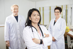 Doctor Standing Arms Crossed While Coworkers Smiling In Clinic. Portrait of confident female doctor standing arms crossed while coworkers smiling in clinic stock photography