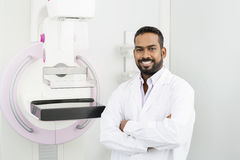 Doctor Standing Arms Crossed By Mammography Machine Royalty Free Stock Image