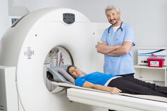 Doctor Standing Arms Crossed By Patient Lying On MRI Machine Royalty Free Stock Photo