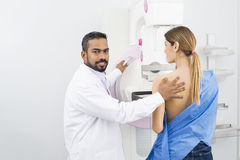 Doctor Standing Assisting Patient Undergoing Mammogram X-ray Tes royalty free stock photo