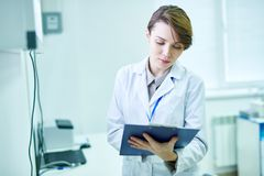 Doctor standing with clipboard and taking notes royalty free stock photography