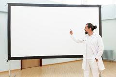 Doctor is standing in front of a empty whiteboard. Giving a lecture or briefing stock photos