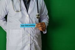 A doctor standing, Hold the Be Healthy paper text on Green background. Medical and healthcare concept royalty free stock images