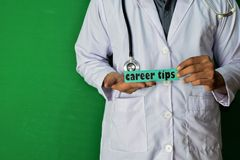 A doctor standing, Hold the Career Tips paper text on Green background. Medical and healthcare concept royalty free stock images