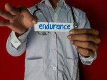 A doctor standing, Hold the endurance paper text on red background. Medical and healthcare concept stock images