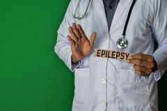 A doctor standing, Hold the Epilepsy paper text on Green background. Medical and healthcare concept royalty free stock images