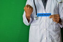 A doctor standing, Hold the Good Health paper text on Green background. Medical and healthcare concept royalty free stock photos