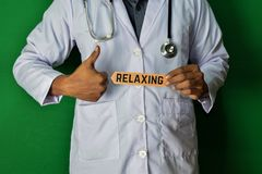 A doctor standing, Hold the Relaxing paper text on Green background. Medical and healthcare concept stock photos