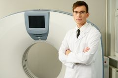 Doctor standing near computed tomography scanner Royalty Free Stock Images