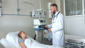 Doctor standing near hospital bed and discussing with young female patient