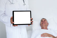 Doctor standing next to the patient and holding a digital tablet Stock Image